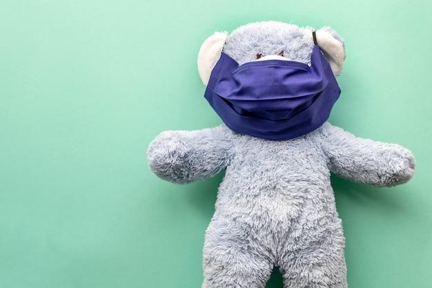 Geneeskunde. blauwe teddybeer in een donkerblauw herbruikbaar masker op een mint effen achtergrond. plaats voor tekst aan de linkerkant