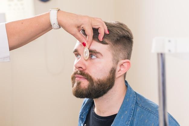 Geneeskunde, gezondheid, oftalmologie concept - oogarts onderzoekt de ogen van de patiënt.
