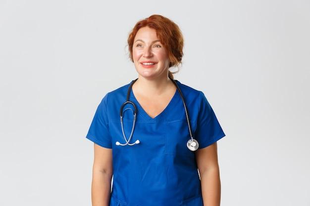 Geneeskunde, gezondheidszorg en coronavirus-concept. gelukkig vermoeide medische werker, vrouwelijke verpleegster in blauwe scrubs kijkt linkerbovenhoek en glimlacht dromerig, prijst lezen voor werken tijdens pandemie.