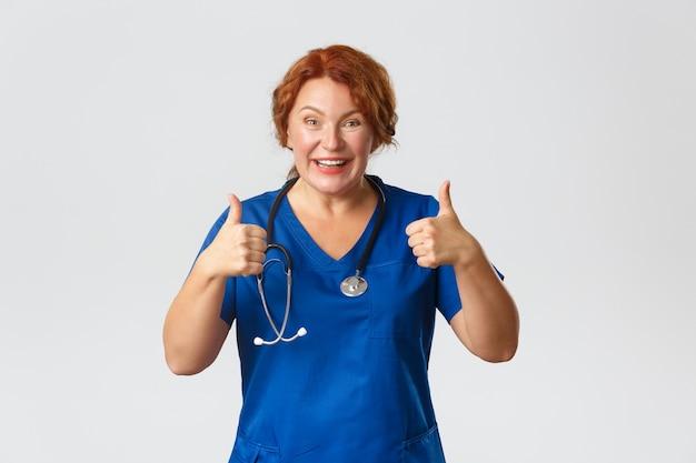 Geneeskunde, gezondheidszorg en coronavirus-concept. vrolijke roodharige arts van middelbare leeftijd raadt kliniekaanbieding of covid-19-testkorting aan, duimen omhoog en glimlachend, keuze goed, grijze achtergrond.