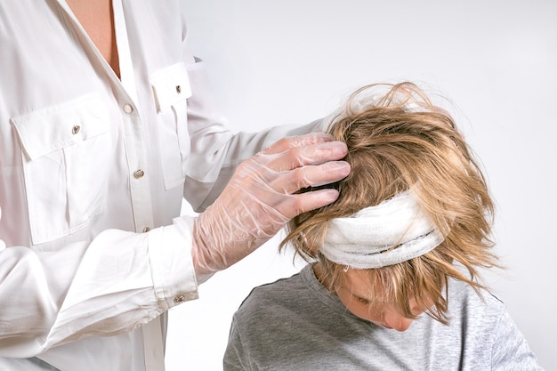 Geneeskunde, gezondheidszorg en pediatrie concept. dokter biedt medische zorg aan een jonge jongen met hoofdletsel. onderzoek, desinfectie, aankleden met een verband. stap voor stap - 1.