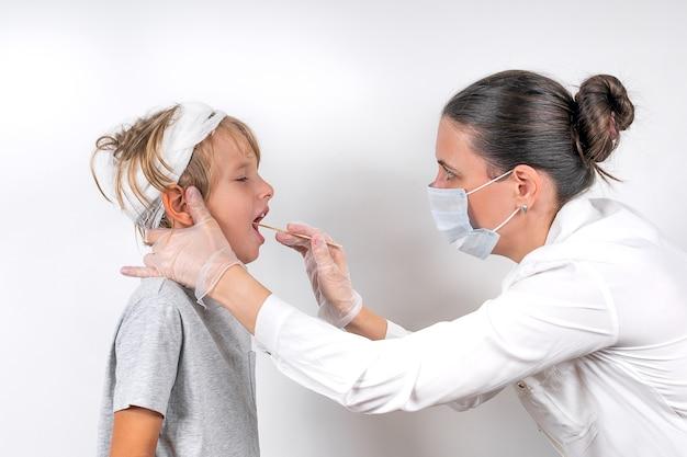 Geneeskunde, gezondheidszorg en pediatrie concept. een vrouwelijke arts met een medisch masker en transparante handschoenen onderzoekt een zieke kleine jongen met hoofdletsel. controleert de keel en neemt een uitstrijkje op het coronavirus.
