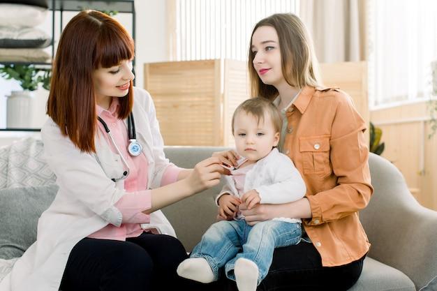 Geneeskunde, gezondheidszorg, kindergeneeskunde en mensenconcept - gelukkige kaukasische vrouwelijke arts of kinderarts die de temperatuur van de baby meten door digitale thermometer op medisch examen bij kliniek