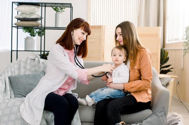 Geneeskunde, gezondheidszorg, pediatrie en mensen concept - jonge vrouw kinderarts controleert adem stethoscoop een klein meisje in de armen van moeder.