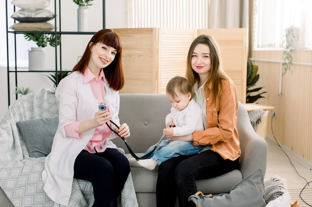 Geneeskunde, gezondheidszorg, pediatrie en mensenconcept - vrouw met baby en jonge vrouwenarts bij kliniek of thuis