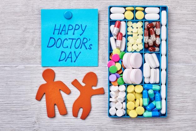 Geneeskunde in container. stickmen op houten oppervlak. gefeliciteerd met een dokter.