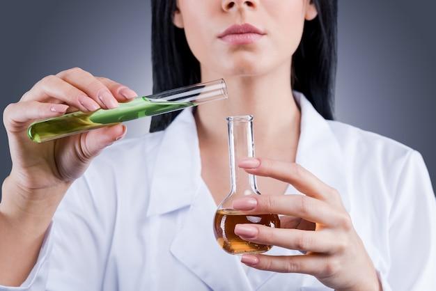 Geneeskunde vooruit. close-up van vrouwelijke arts in wit uniform die kolven vasthoudt terwijl ze tegen een grijze achtergrond staat