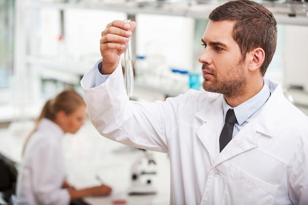 Geneeskunde vooruit. zelfverzekerde jonge mannelijke wetenschapper die een reageerbuis vasthoudt terwijl zijn vrouwelijke collega op de achtergrond werkt