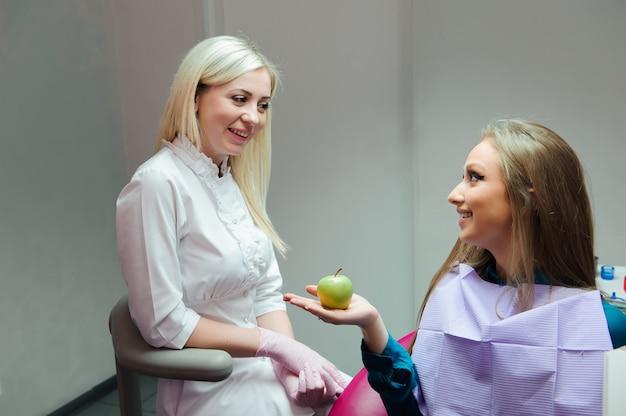 Geneeskundeconcept - vrouwelijke arts die een appel geven aan de patiënt