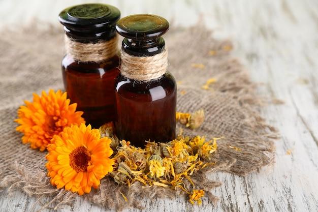 Geneeskundeflessen en calendulabloemen op houten tafel
