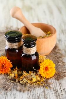 Geneeskundeflessen en calendulabloemen op houten