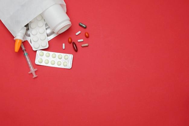 Geneeskundepillen op rode achtergrond, ruimte voor tekst. geneeskunde drogisterij concept