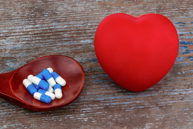 Geneeskundepillen, tabletten en capsules op houten lepel met hart.
