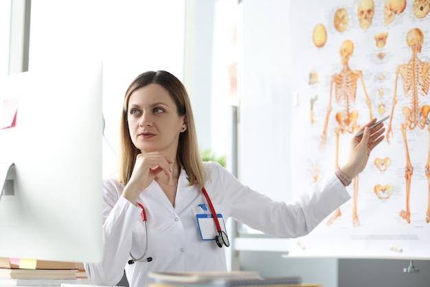 Geneeskundeprofessor kijkt naar computerscherm en toont pen op poster met menselijk skelet