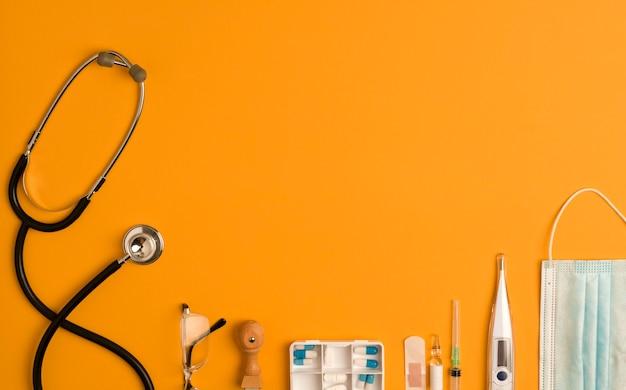 Geneeskundetoebehoren, stethoscoop, blocnote en pen, oranje achtergrond met exemplaarruimte.