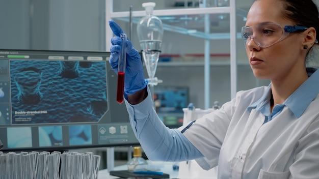 Geneeskundewetenschapper die computer gebruikt terwijl hij een reageerbuis vasthoudt