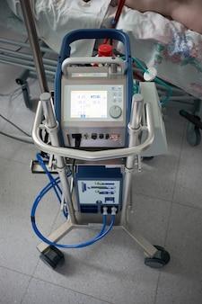 Geneesmiddel. extracorporale membraanoxygenatie. werkende ecmo-machine op de afdeling intensive care. close-up oxygenator van ecmo. ernstig zieke patiënt op achtergrond.
