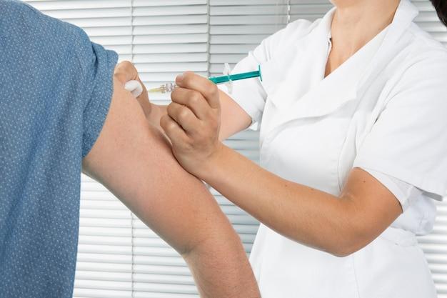 Geneesmiddelinjectie in de arm gemaakt door vrouwelijke arts