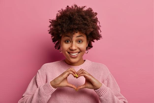 Genegenheid en relatie concept. blij dat etnische opgetogen vrouw hart met handen vormt, positief glimlacht, liefdesymbool toont, roze pasteltrui draagt, gebaren binnen. monochroom schot