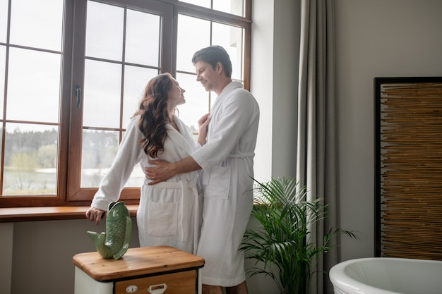Genegenheid. twee mensen in witte badjassen die bij het raam staan en er aanhankelijk uitzien
