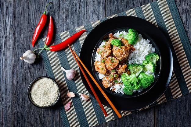 General tso's chicken krokante chinese kippenbeten in een zwarte kom met rijst en gestoomde broccoliroosjes, horizontale weergave van bovenaf, plat gelegd