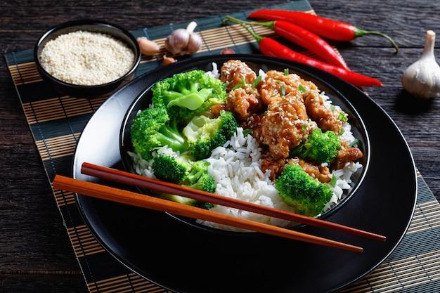 General tso's chicken krokante chinese kippenbeten in een zwarte kom met rijst en gestoomde broccoliroosjes, horizontale weergave van bovenaf