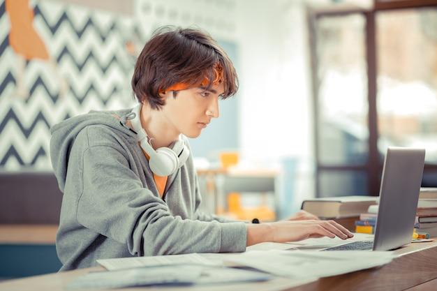 Generatie z. de tiener doet zijn hometaak met behulp van de computer
