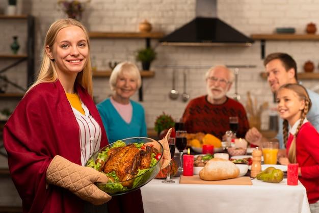 Generaties van het gezin aan de thanksgiving-tafel en moeder die de kalkoen brengt