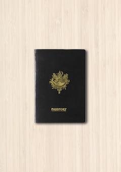 Generiek zwart paspoort dat op witte houten achtergrond wordt geïsoleerd