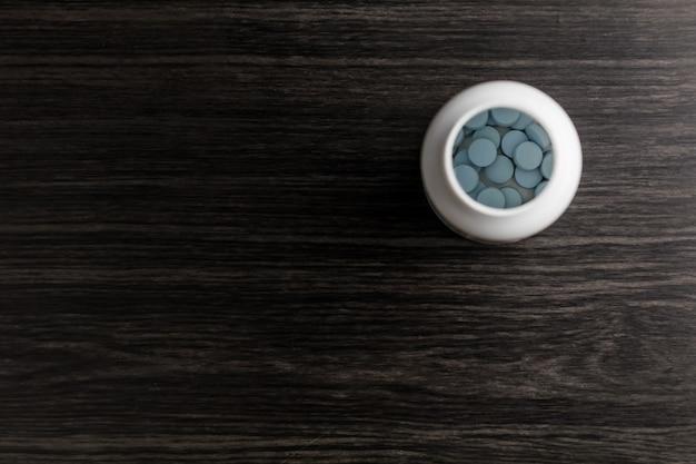 Generische blauwe erectiestoornissen pillen in een fles op hout achtergrond. bekijken met kopie ruimte.