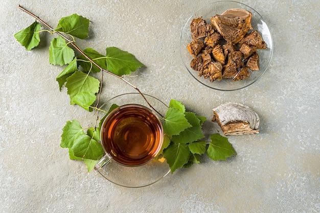 Genezende infusie van chaga-berkpaddestoelen in glazen bekers en chaga-stukjes op een houten tafel