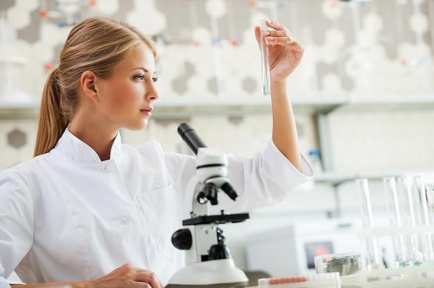 Genezing ontdekken. geconcentreerde jonge vrouwelijke wetenschapper die een reageerbuis vasthoudt en ernaar kijkt terwijl ze op haar werkplek zit