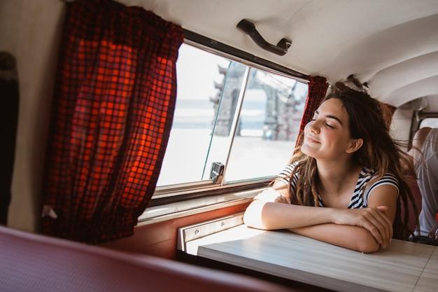 Geniet de portret jonge vrouw die van zonnestraal ontspannen