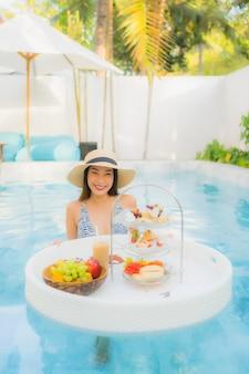 Geniet de portret mooie jonge aziatische vrouw van met middagthee of ontbijt drijvend op zwembad