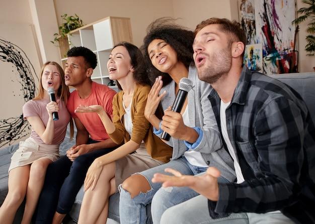 Geniet gewoon van het moment dat een groep multiculturele vrienden enthousiast kijkt terwijl ze karaoke spelen bij