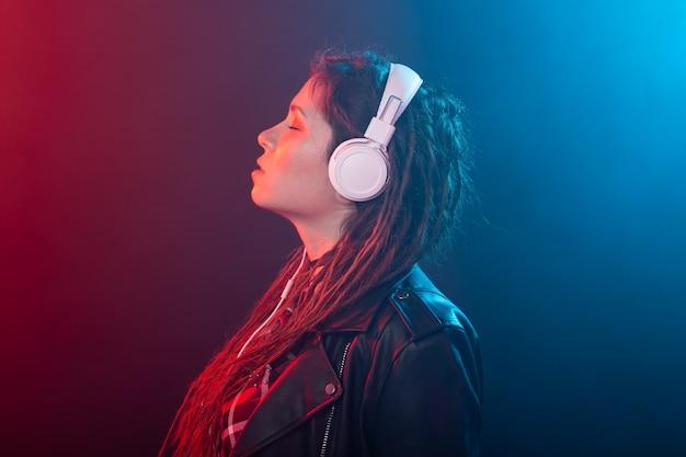 Geniet, meloman en mensen concept - jonge vrouw met dreadlocks luisteren naar de muziek, portret
