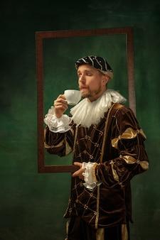 Geniet van aroma. portret van middeleeuwse jonge man in vintage kleding met houten frame op donkere achtergrond. mannelijk model als hertog, prins, koninklijk persoon. concept vergelijking van moderne tijdperken, mode.