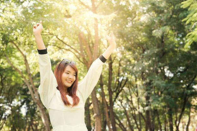 Geniet van de natuur. jonge aziatische vrouwelijke armen hebben zich genoten van de frisse lucht in het groene bos.