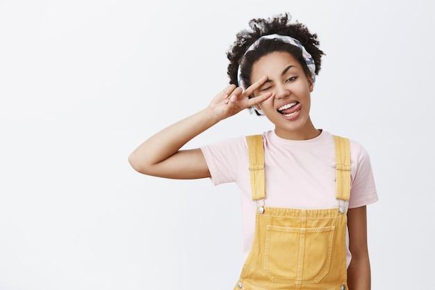 Geniet van het leven en relax. portret van vrolijke, zorgeloze mooie afrikaanse amerikaan in gele overall en hoofdband, kantelend hoofd, tong tonen en vredesteken maken over oog, knipogen, plezier hebben