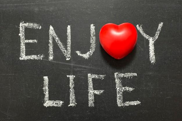 Geniet van het leven zin handgeschreven op schoolbord met hartsymbool in plaats van o