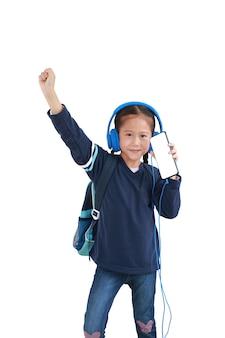 Geniet van het portret gelukkig aziatisch klein jong geitjemeisje met smartphone en hoofdtelefoons die op wit wordt geïsoleerd
