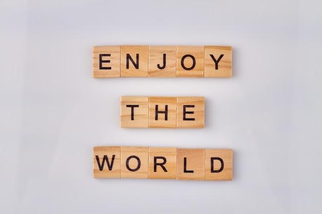 Geniet van het wereldconcept. inspirerend citaat gemaakt van houten letterblokken op witte achtergrond.