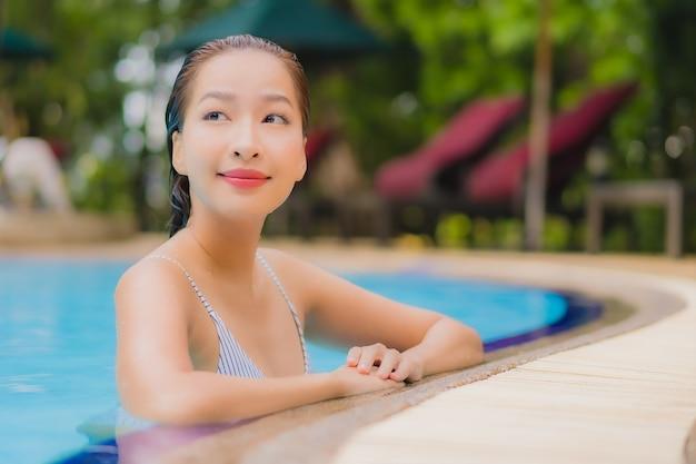 Geniet van ontspannende glimlachvrije tijd van de portret mooie jonge aziatische vrouw rond openluchtzwembad in hotel
