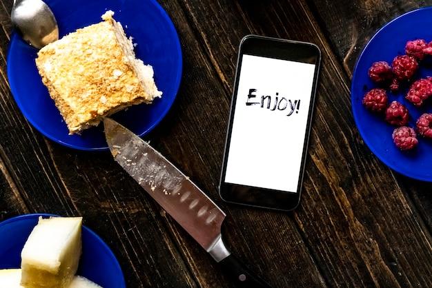 Geniet van tekst op een smartphone met zoet voedsel op houten tafel plat lag concept f