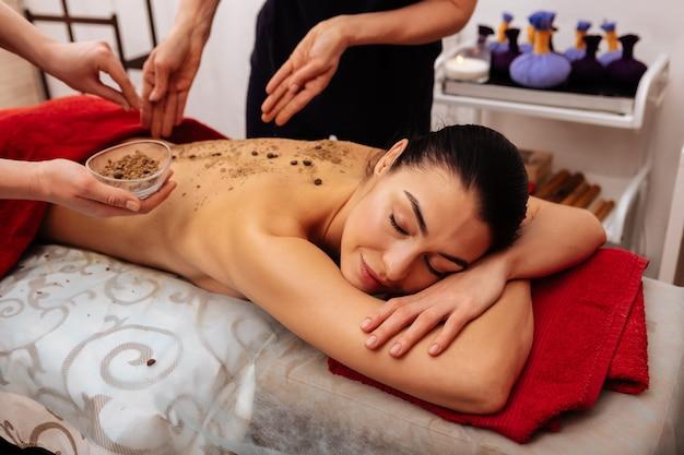 Genieten van alle voordelen. slaperige mooie vrouw die haar hoofd op gekruiste handen zet terwijl de werknemer haar rug bedekt met zand en bonen