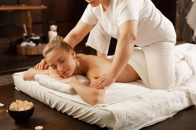 Genieten van bewegingen. masseuse in wit uniform zittend op de rug van haar cliënt en omgaan met schouders