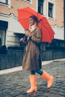 Genieten van de herfst in de stad. volledige lengte van aantrekkelijke jonge lachende vrouw in rubberen laarzen met paraplu en koffiekopje terwijl ze op straat loopt