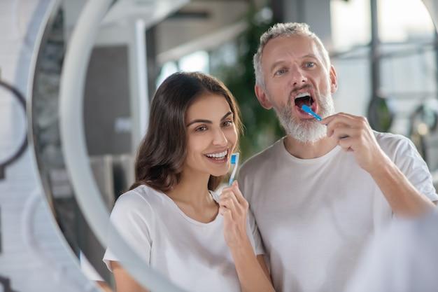 Genieten van de ochtend. een man en een vrouw die samen hun tanden poetsen