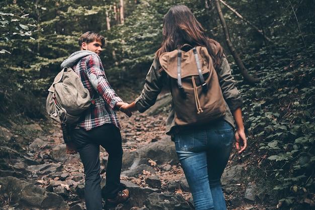 Genieten van de reis. achteraanzicht van een modern jong stel dat handen vasthoudt en omhoog beweegt terwijl ze samen wandelen in het bos