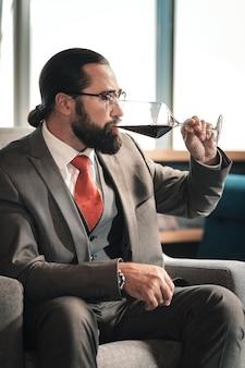 Genieten van de smaak. ervaren bebaarde donkerharige advocaat die na een werkdag geniet van de smaak van rode wijn